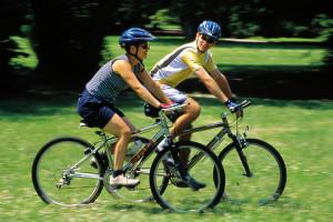 Pasangan muda-mudi sedang berolahraga sepeda santai di padang rumput.